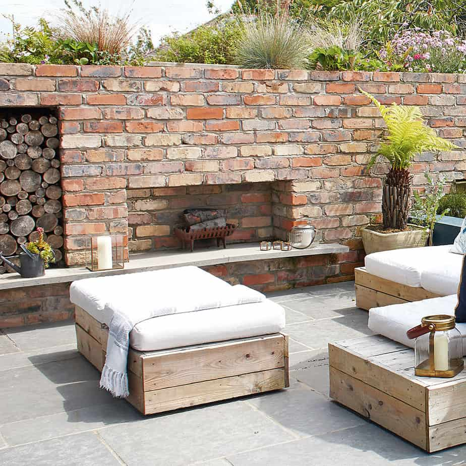 A garden with stone walls, outdoor seating area and a fireplace