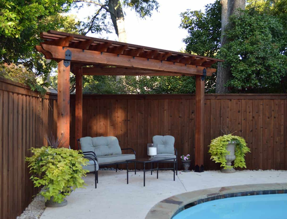A pergola installed in the corner of the garden with a view of the swimming pool
