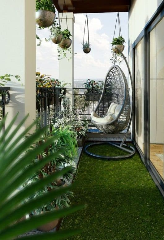 A small balcony with simple hanging plants and a comfortable, modern chair