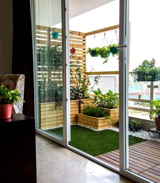 Artificial grass, decking and plenty of plants in a small balcony