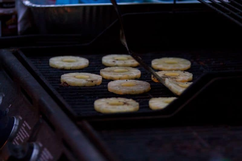 Chunks of pineapple being grilled on a gas BBQ grill