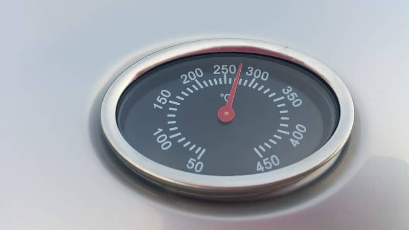 A built-in thermometer on a gas grill's lid cover