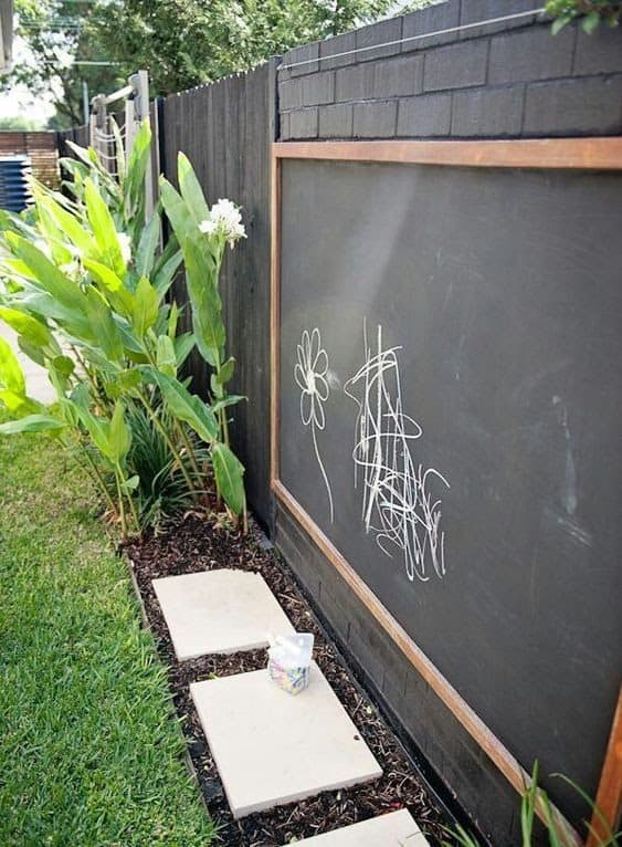 A blackboard installed along a wall for kids to practice drawing outdoors