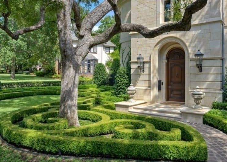 A front yard with mini garden maze made from hedges