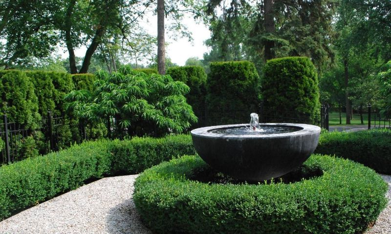 Garden hedges as a natural backdrop for a semi-globe water feature
