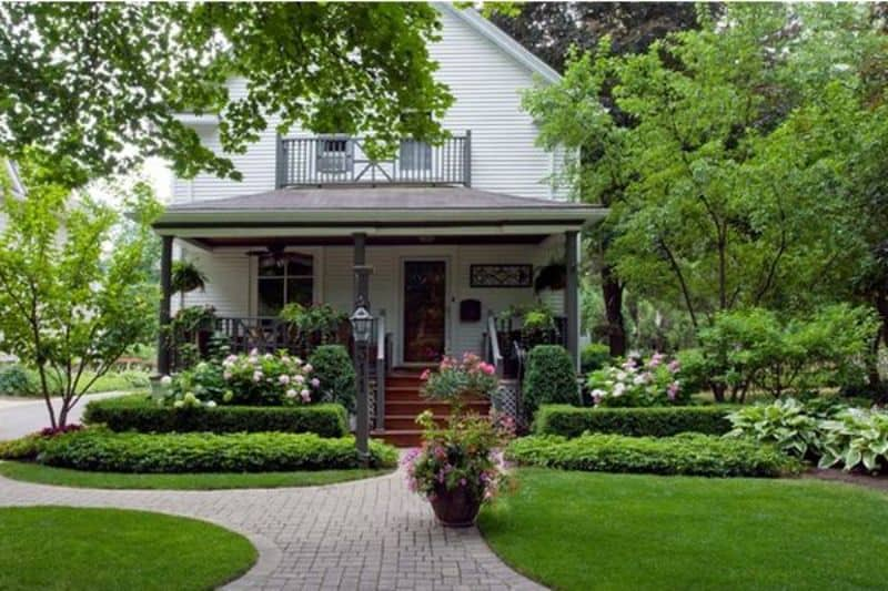 front porch with circular patches of lawn and low hedges