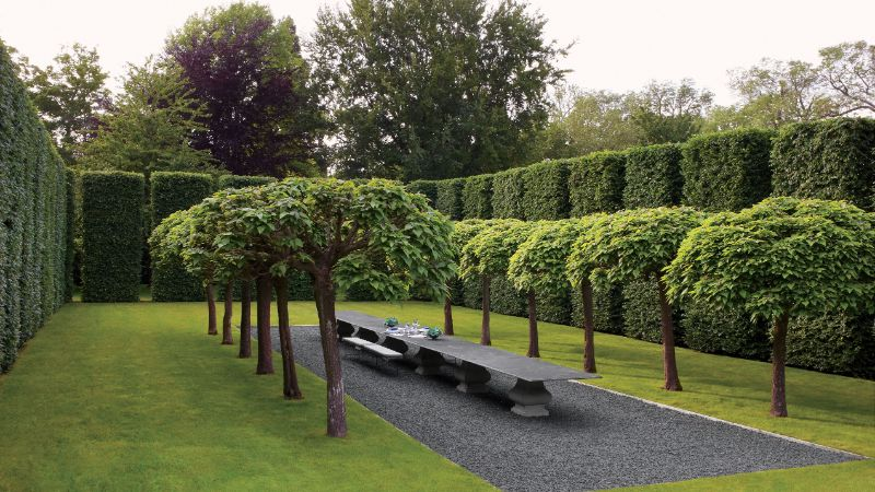 tall hedges surrounding lines of trees either side of a gravel path and stone table