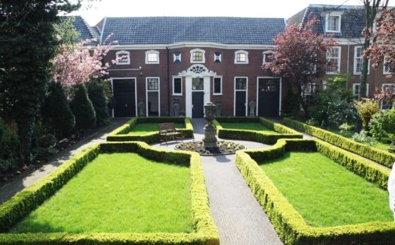 Outlined garden hedges outside a large house with a fountain or statue