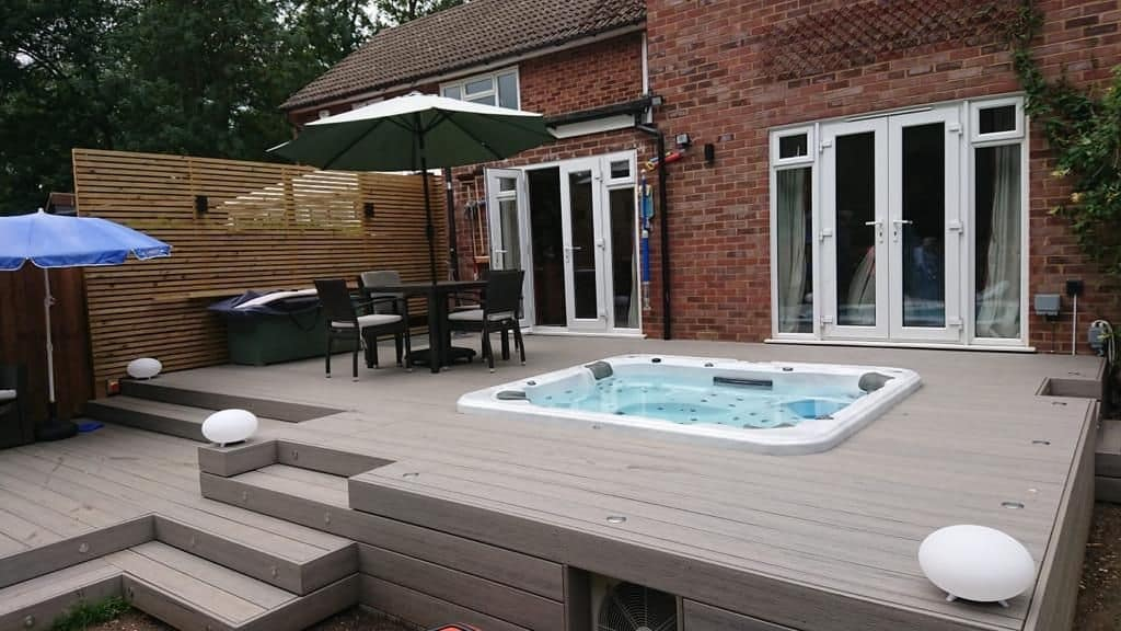 A hot tub deck with composite decking material