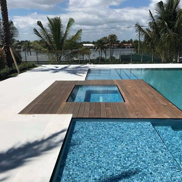 A pool and a hot tub combined with wooden deck as a barrier