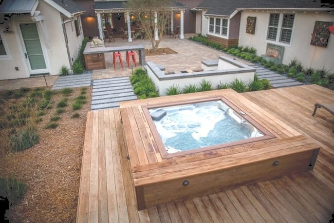 A hot tub with natural wooden decking that complements any garden setting