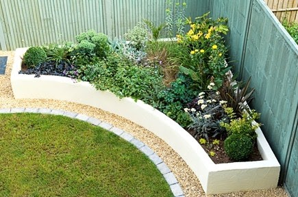 A corner garden bed with an attractive semi-circular raised garden bed and plant
