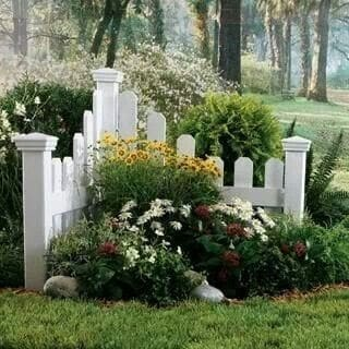 Corner flower beds with a small section of fencing