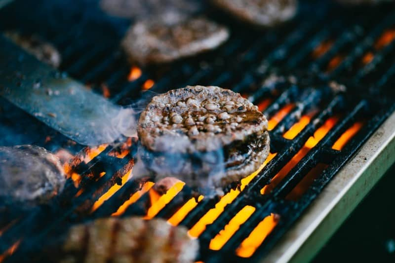 Burger patties being cooked on a grill with direct heat