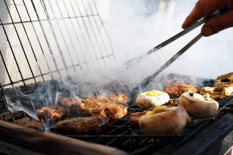 A variety of dishes on a charcoal BBQ grill with indirect heat