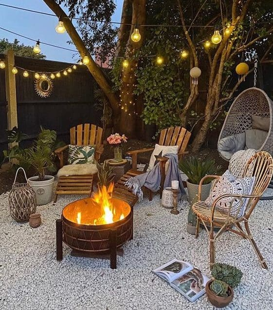 Fire pit on pebble floor with string lights and outdoor seating