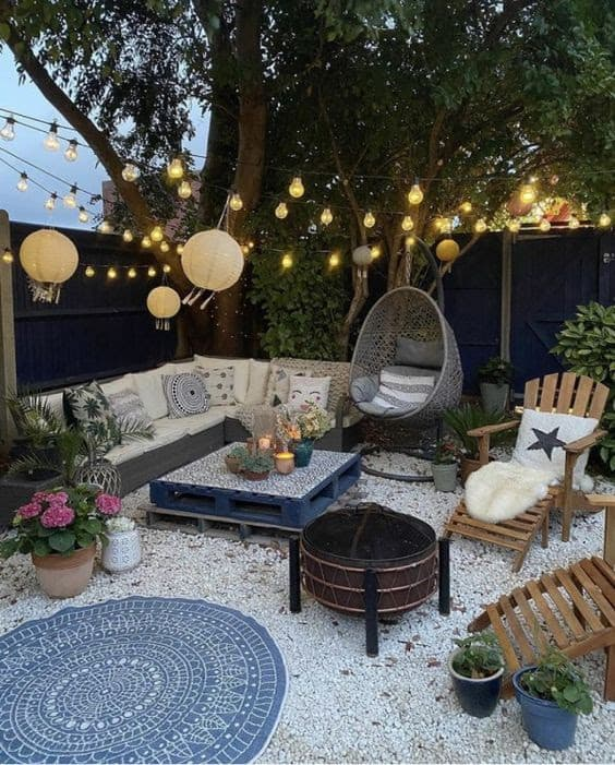 DIY outdoor lounge with comfy seating area, rug, and pretty lights