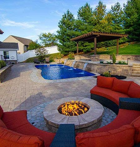 A fire pit near to a swimming pool