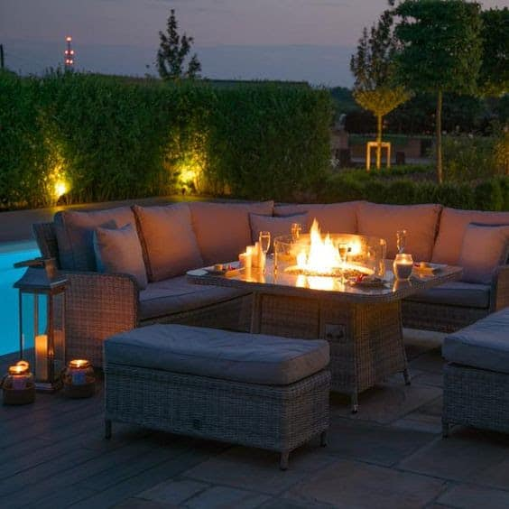 An outdoor dining table with fire pit in the middle