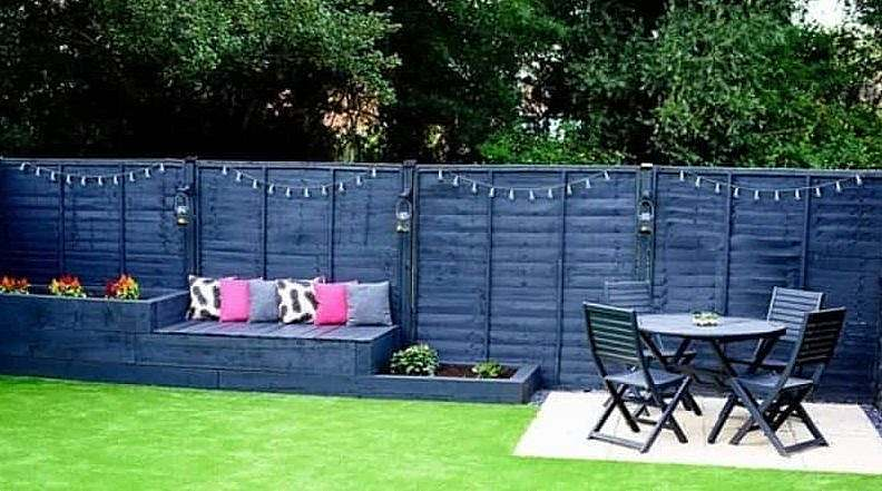 A fence painted in blue with a patio set and raised planters