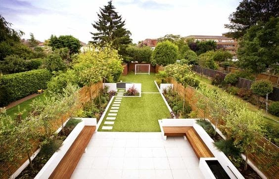 Modern long garden with a large seating area with a patio, a lush green lawn with stepping stones and a football field