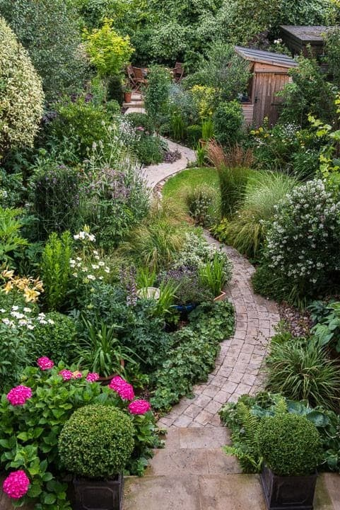 A brick winding path and more natural planting around