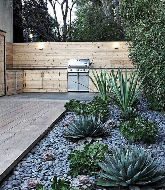 Deserted-style garden with wood decking, stone beds and succulents