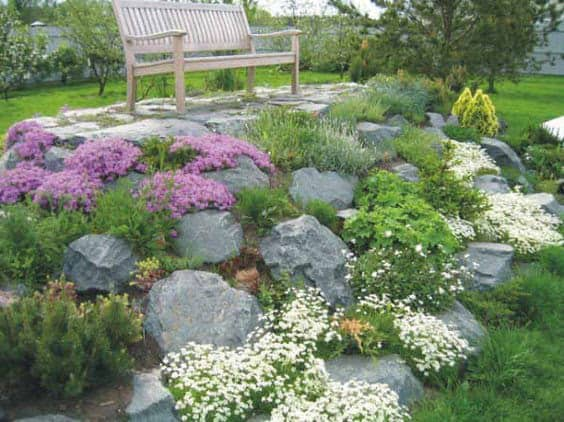 A rock formation that gives the garden some extra height, with a bench on top
