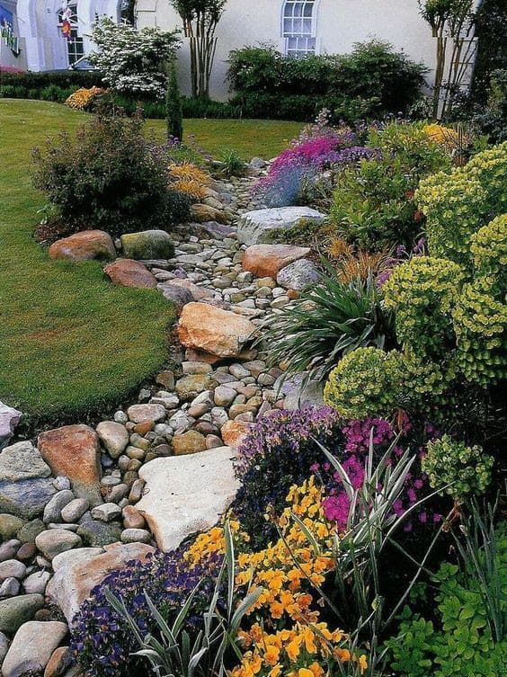 Stones and rocks are used to create a dry river bed in a garden