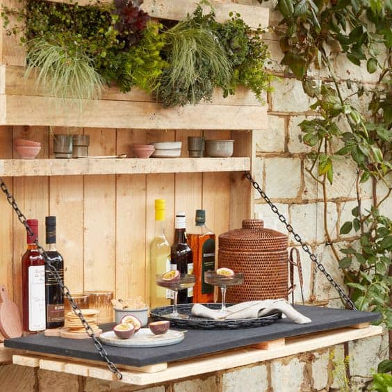 A side garden bar that features built-in planter for decoration and a sturdy table top for eating and drinking
