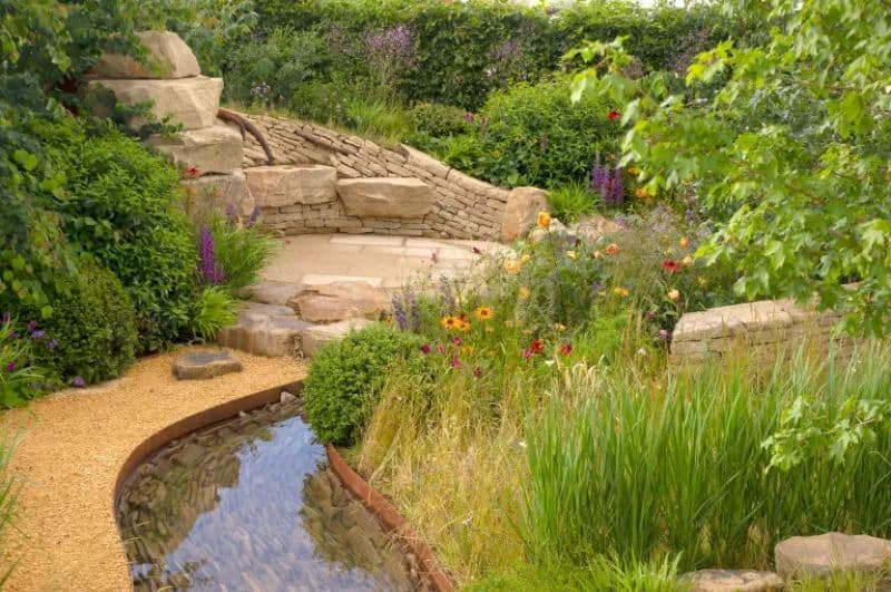 A natural landscape with flowing water feature curves with dry stones and plants around