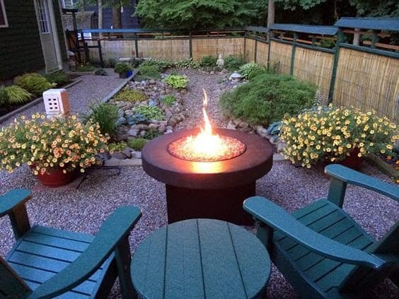 A modern fire pit with a pebble path