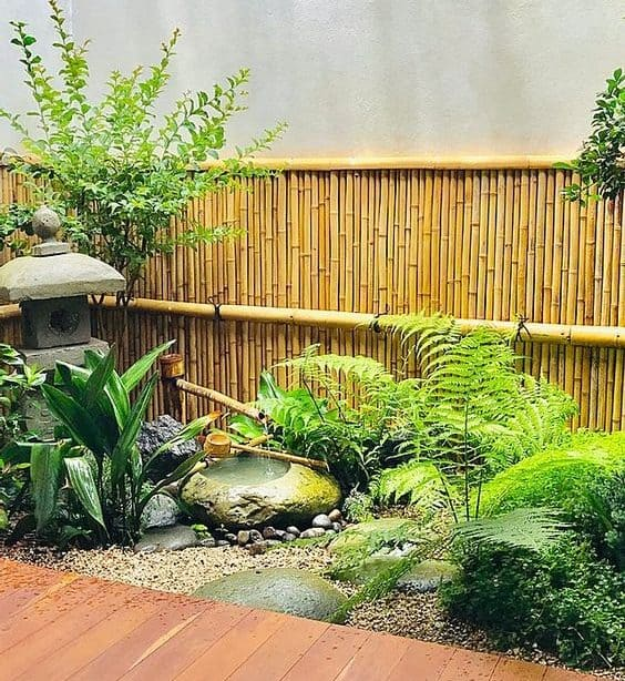 A miniature zen garden with some bamboo fencing, a stone water feature and leafy greenery