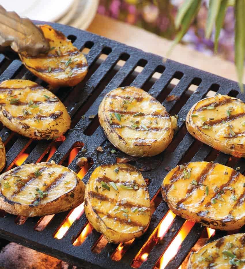 Sliced potatoes being grilled on a charcoal grill