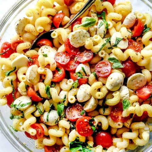 Caprese pasta salad in a large clear bowl