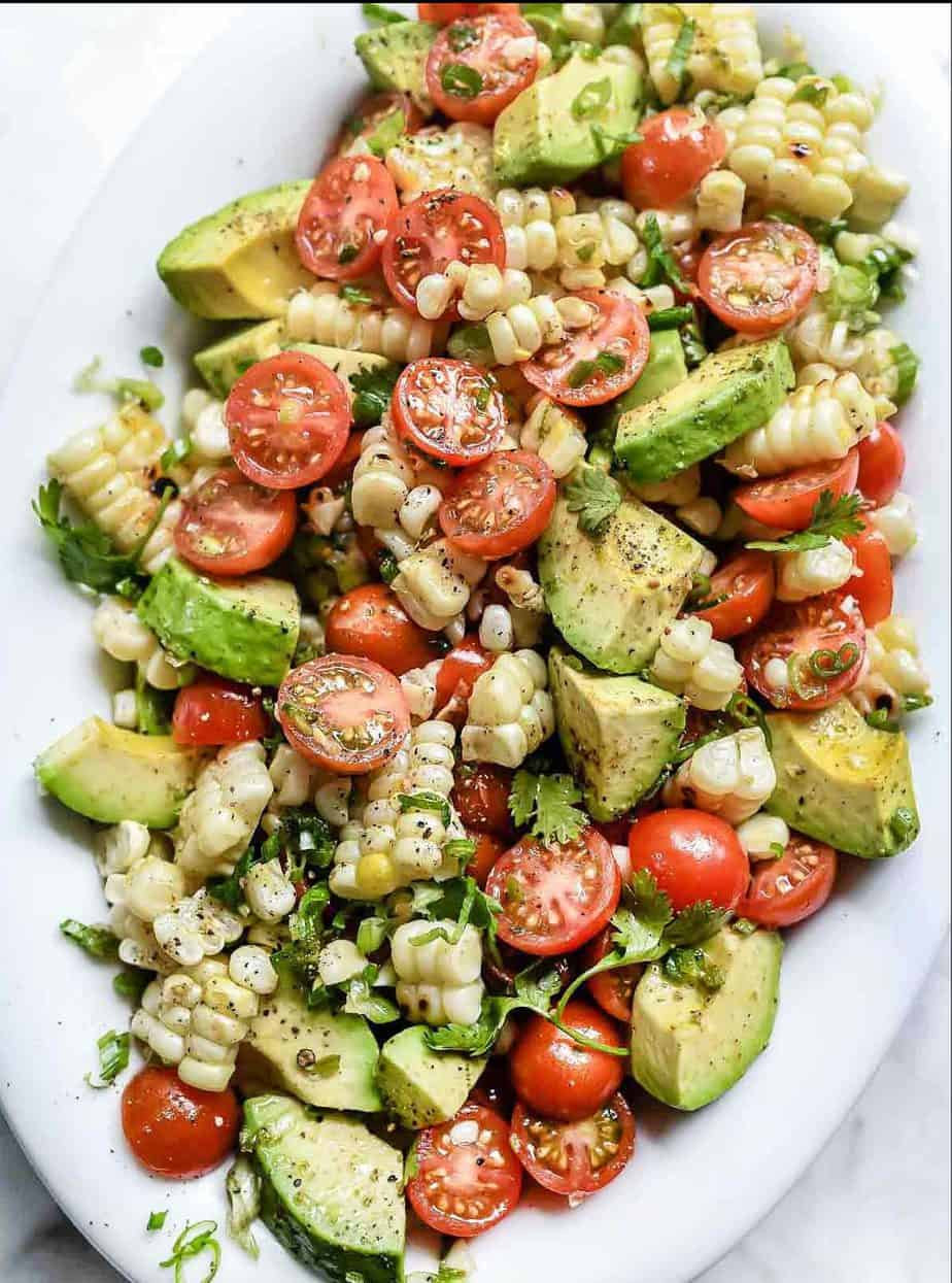 A healthy bowl of salad with corn, tomato, and avocado