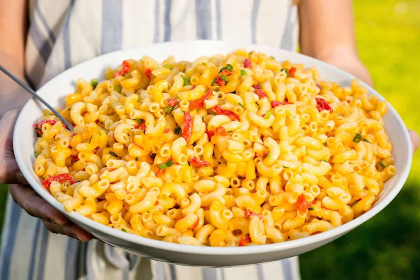 A large plate of pimento cheese pasta salad being served outdoors