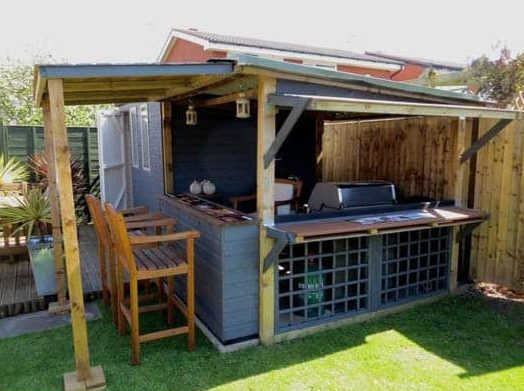A medium-sized wooden shack that houses both BBQ grill and bar setup