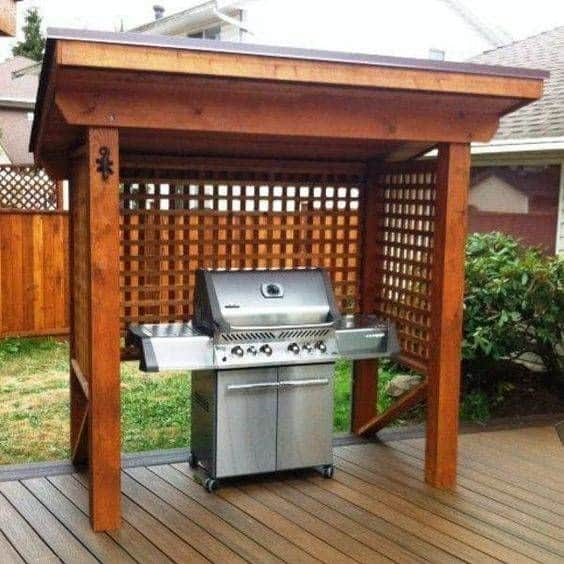 A classic-style wooden gazebo used as a BBQ shelter
