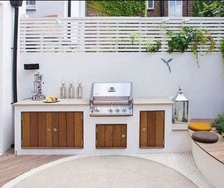 Small white BBQ area with wooden cabinets