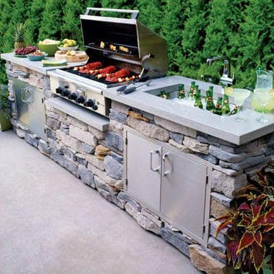 Stone outdoor kitchen with a sink and storage cabinets