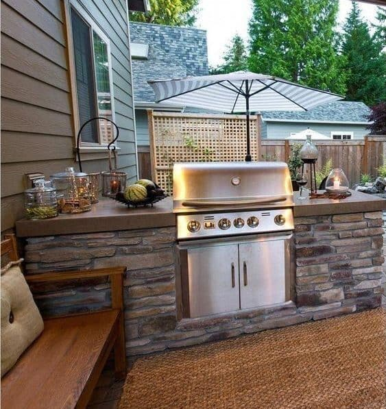 Small stone BBQ area with bench next to it