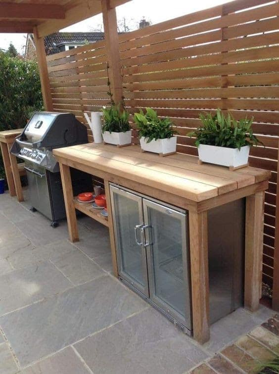DIY wood BBQ area decorated with potted plants