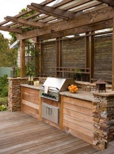 Rustic BBQ area made from weathered wood panels and stone walls
