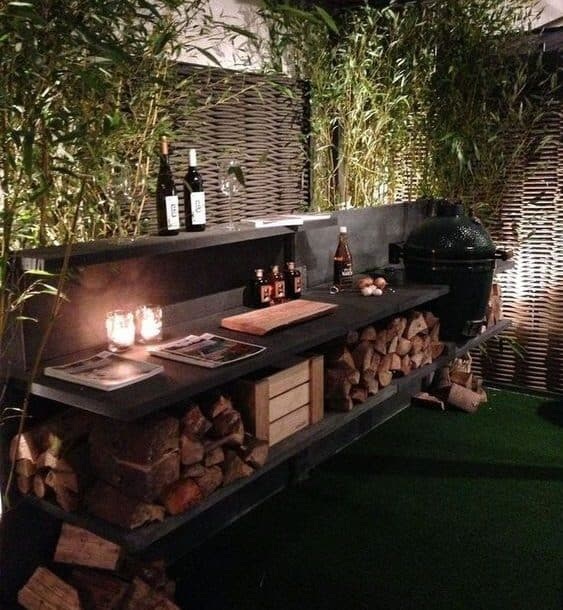 A modern outdoor kitchen area surrounded with wood and plants