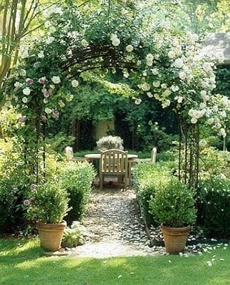An archway at the garden entrance decorated with pretty climbing flowers