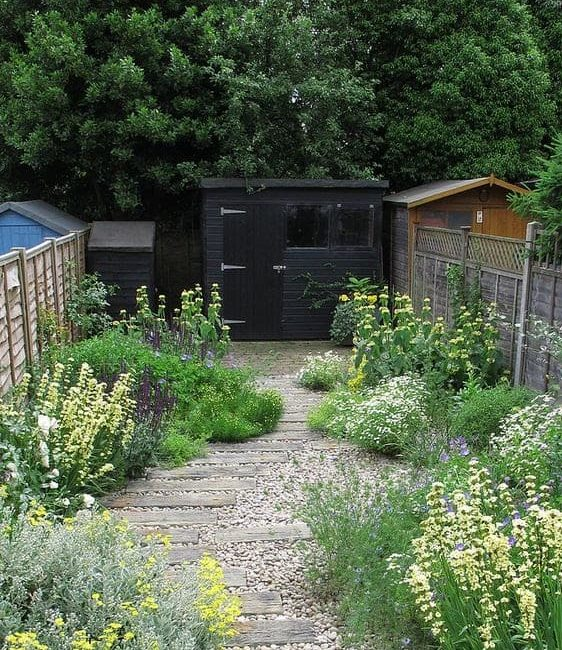 Modern black shed in a contemporary garden setting with bright and colourful flowers