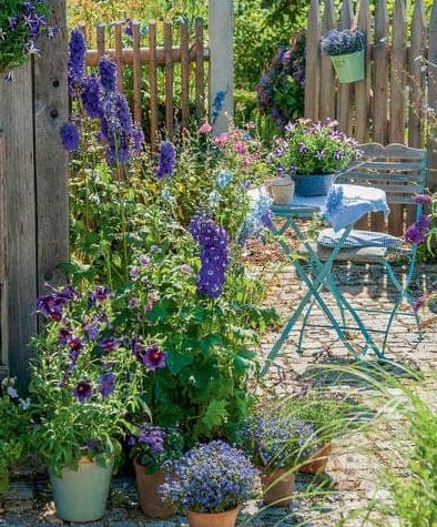 Cottage garden with flowers and furniture in blue tones
