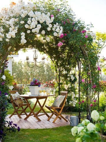 Outdoor table dining set under flower arch