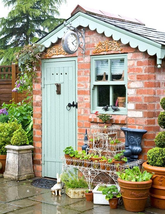 A small brick shed with potted plants at the front
